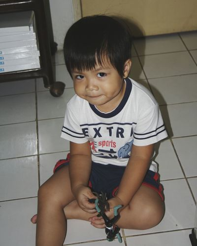Portrait of boy playing on floor at home