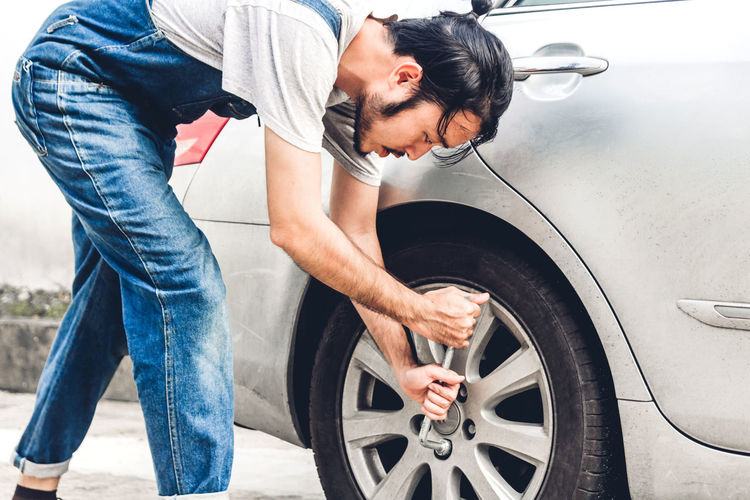 Man repairing car outdoors