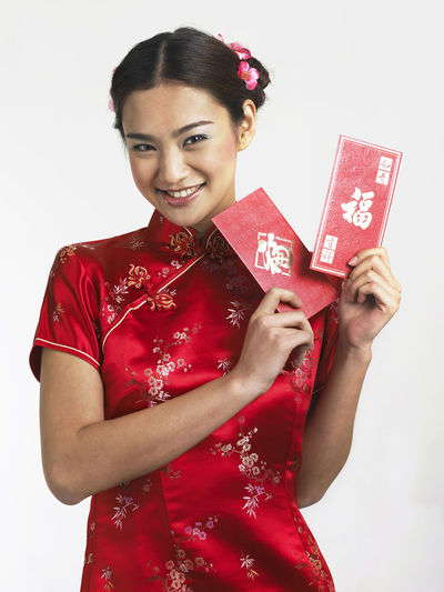 chinese woman holding red envelope -angpao Gong Xi Fa Cai Greeting Prosperity Traditional Clothing Ang Pao Cheerful Chinese New Year Day Happiness Holding Indoors  Looking At Camera One Person Portrait Red Red Envelopes Smiling Studio Shot Traditional Clothing White Background Young Adult Young Women