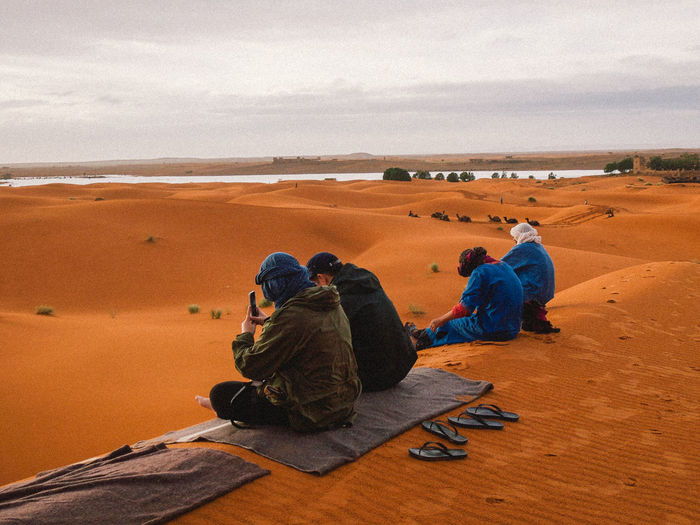 People Sitting On Sand Dune In Desert