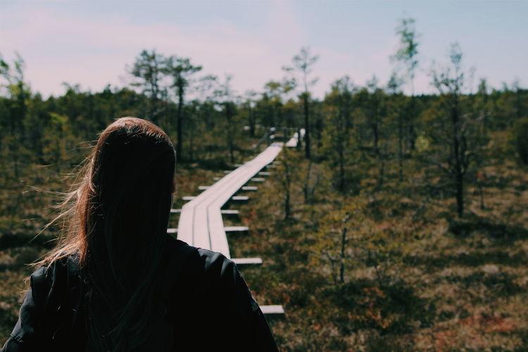 Rear view of woman walking on boardwalk against sky