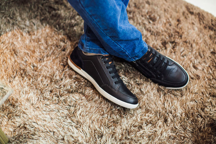 Low section of man wearing shoes on rug