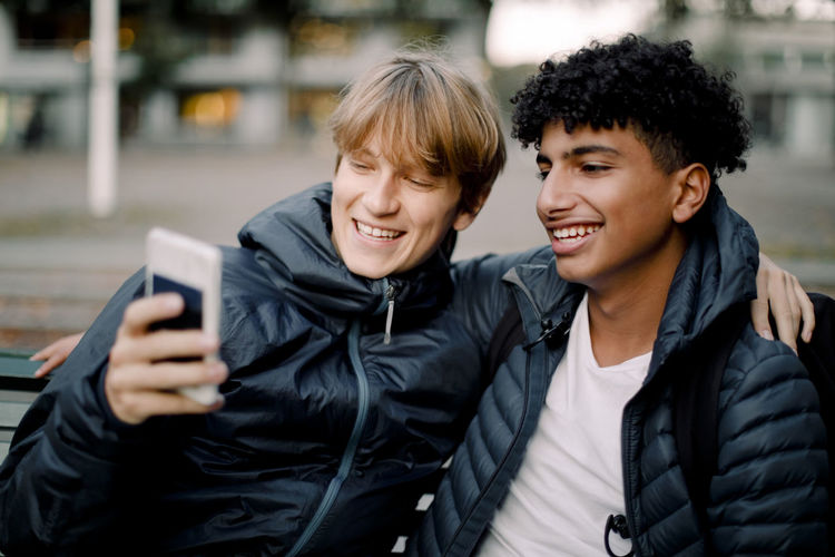 Portrait of smiling young man using mobile phone at camera