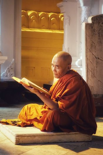 Monk reading book while sitting in temple