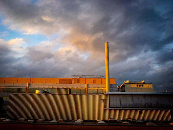 Low angle view of yellow factory against sky