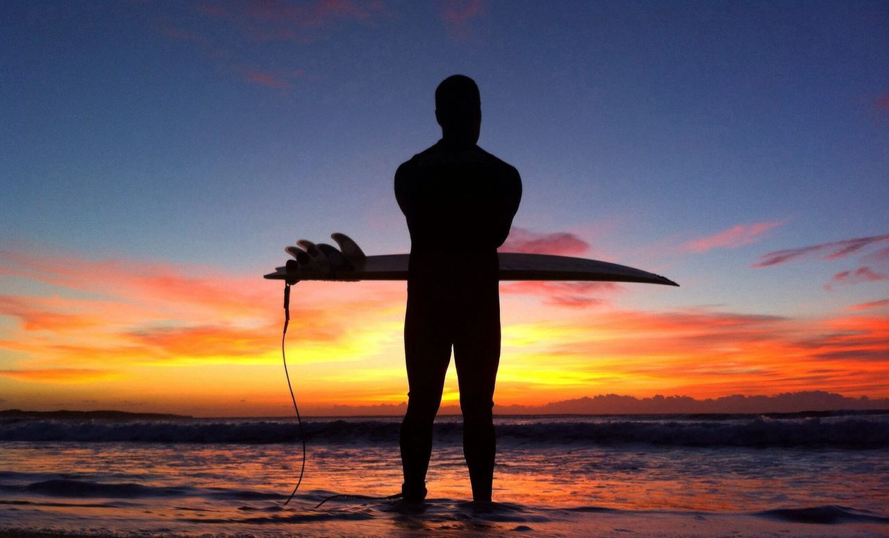 Silhouette man carrying surfboard on beach