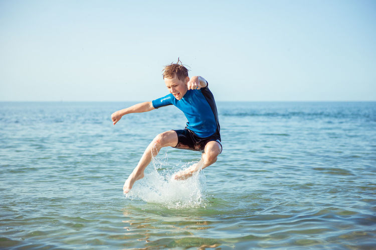 Full length of boy jumping in sea water against sky