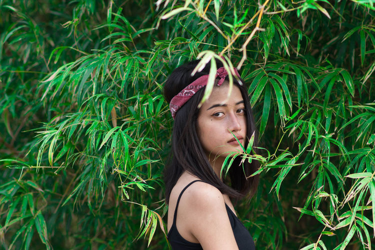 Side view portrait of young woman by plants