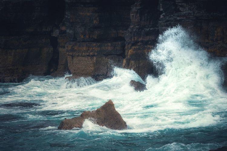 Waves splashing on rocks at sea
