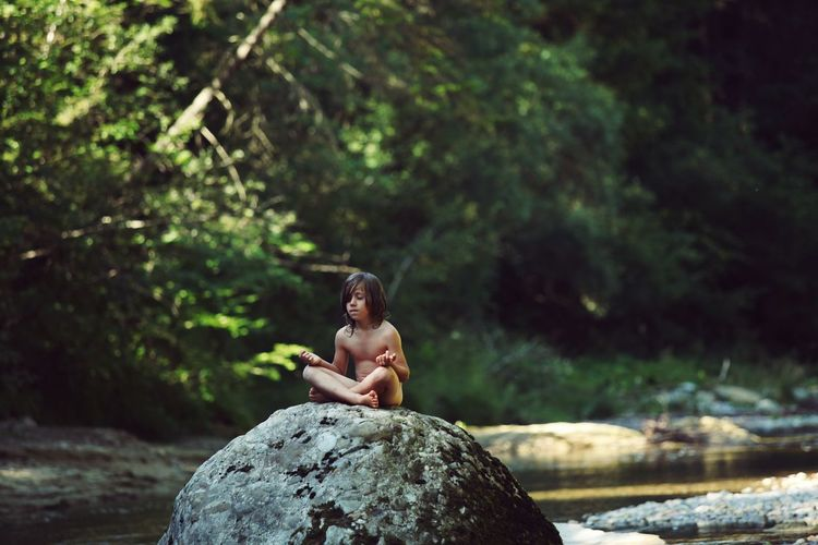 Boy Sitting On Stone By Water