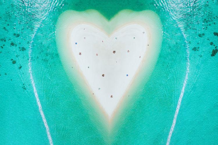 Aerial view of heart shape beach amidst sea