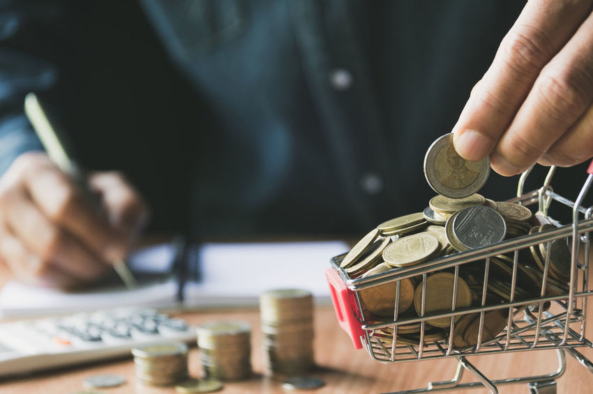 Hand holding a coin with pile of coin in the shopping cart for accounting and business concept. Human Hand Hand Real People One Person Holding Human Body Part Midsection Coin Focus On Foreground Indoors  Men Finance Close-up Day Art And Craft Technology Occupation Selective Focus Container