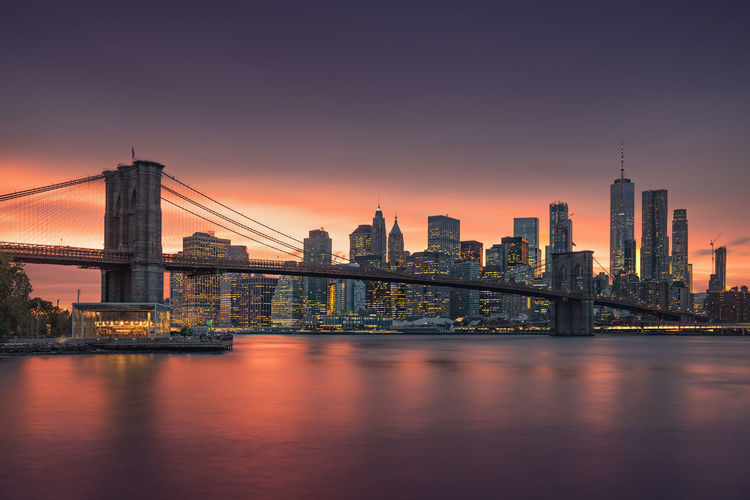 Brooklyn bridge over river with buildings in background during sunset