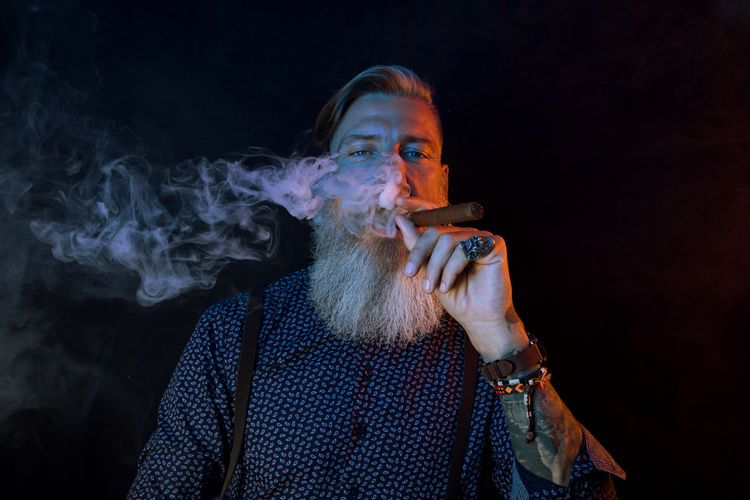 Mature Hipster Smoking Cigar Against Black Background