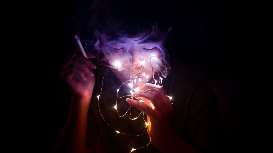 Close-up of man smoking while holding illuminated lighting equipment against black background