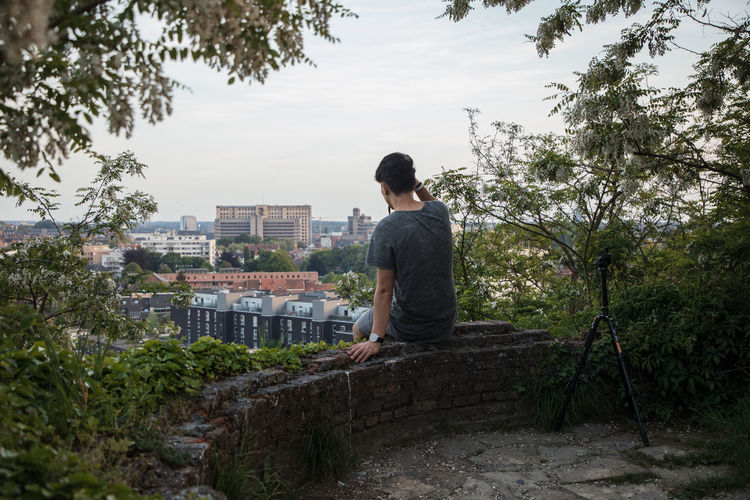 Man Sitting On Retaining Wall Amidst Trees In City