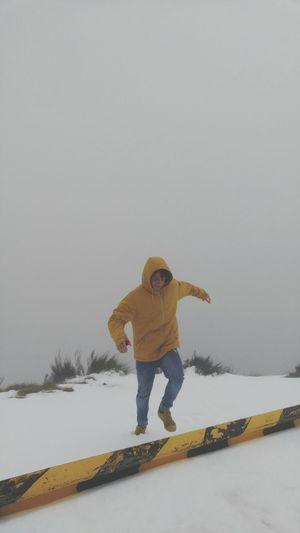 Full length of girl standing on snow covered landscape against clear sky