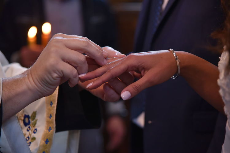 Cropped image of bridegroom inserting wedding ring in bride finger