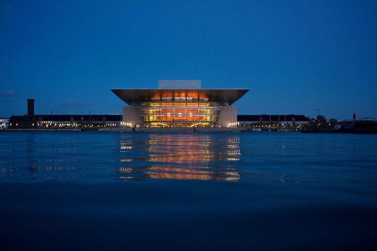 Illuminated building by sea against blue sky