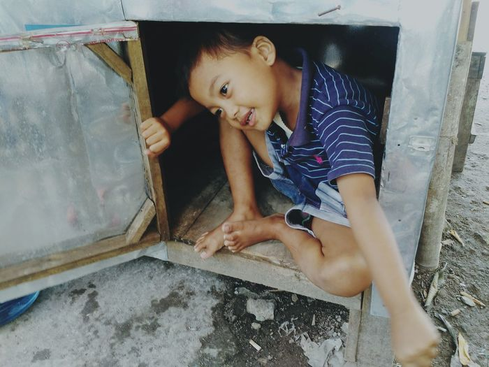 Playful boy sitting in abandoned cabinet