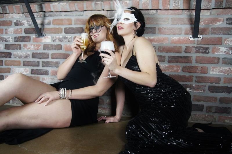 Female friends wearing masks holding drink glasses against brick wall