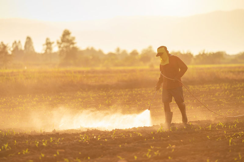 Full length of man spraying pesticides on field against sky during sunset