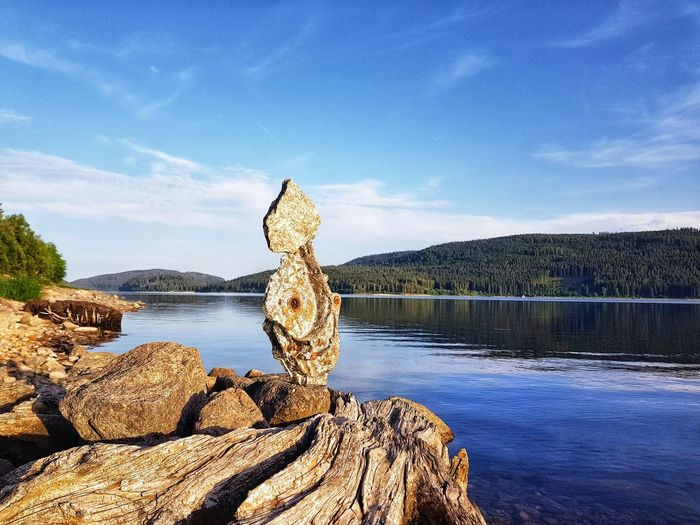 Scenic view of lake against sky with rock formation