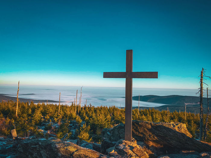 Scenic view of cross against clear blue sky