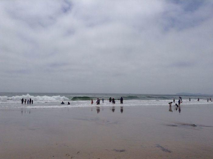 People at beach against sky