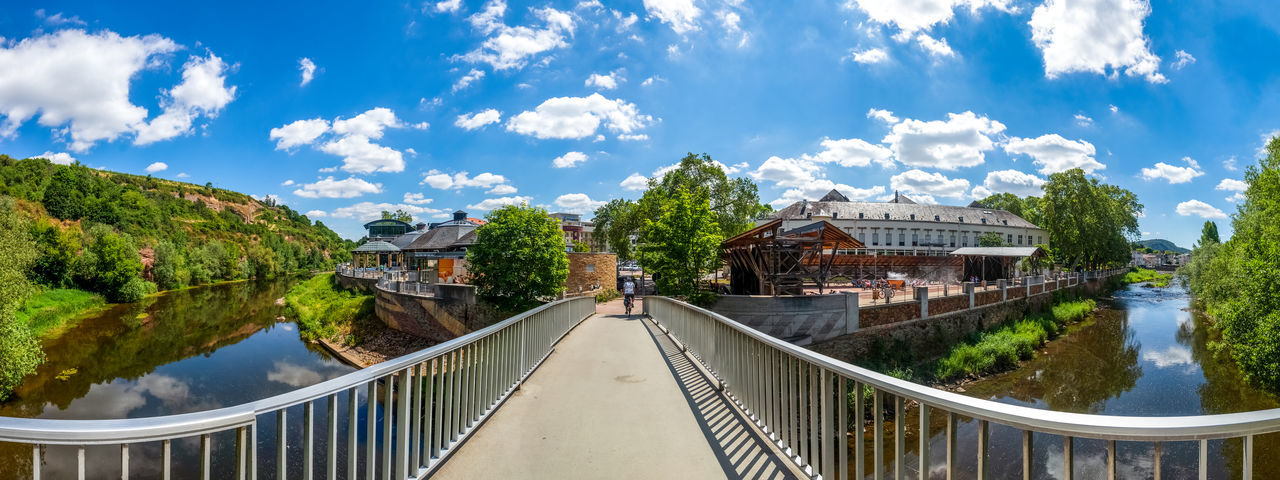 Panoramic view of bridge over canal in city against sky