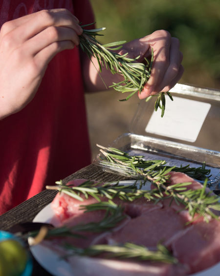 Midsection Of Person Holding Rosemary With Pork Chops On Table