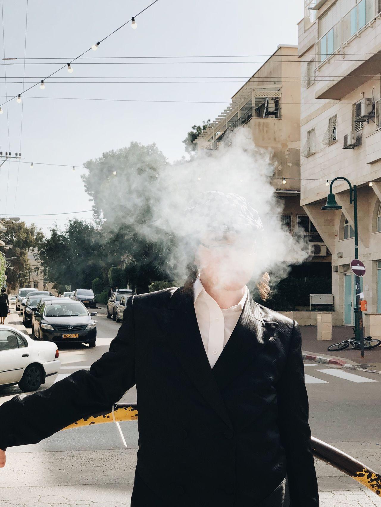 Close-up of man smoking on city street