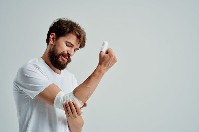 Young man holding hands against white background