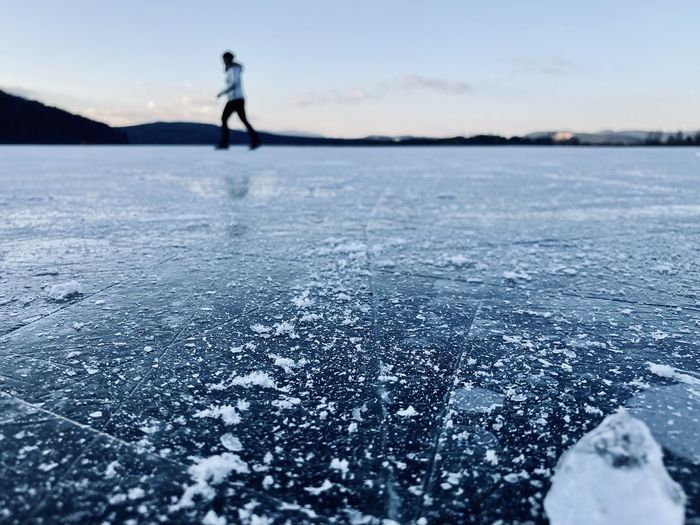 Person standing in frozen lake against sky during winter