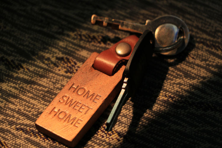 Home Domestic Life Keychain Key Protection Lock Access Home Sweet Home Indoors  Table Still Life No People Close-up Text High Angle View Antique Western Script Wood - Material Communication Shadow Safety Security Sunlight Carpet - Decor