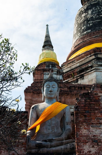 The ruins include a Buddha image and a pagoda made of brick. Ancient Archaeological Site Respect Ruins Stupa Architecture Attractions Bricks Buddhism Day Golden Color History Human Representation Idol Low Angle View Male Likeness No People Outdoors Place Of Worship Religion Sculpture Sky Spirituality Statue Yellow Robe