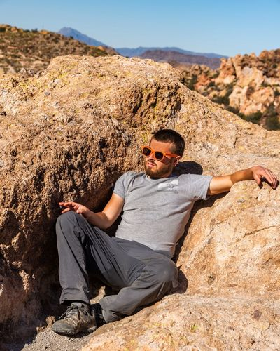 Full length of man sitting on rock during sunny day
