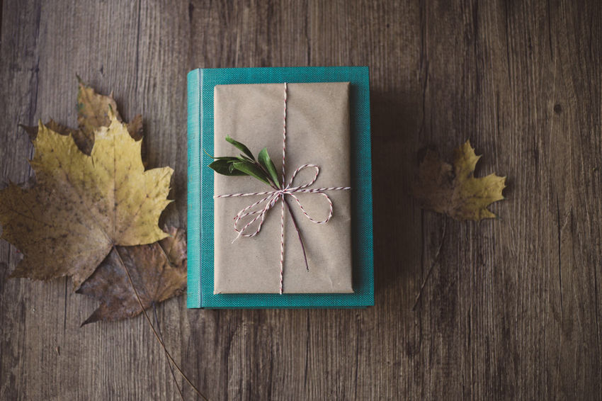 Wrapped gifts on wooden table Christmas Holiday Love Wrap Chritsmas Decoration Gift Paper Wrapped Close-up High Angle View Dried Plant Table No People Fragility Nature Indoors  Wood - Material Anise Day Directly Above Leaf Flower
