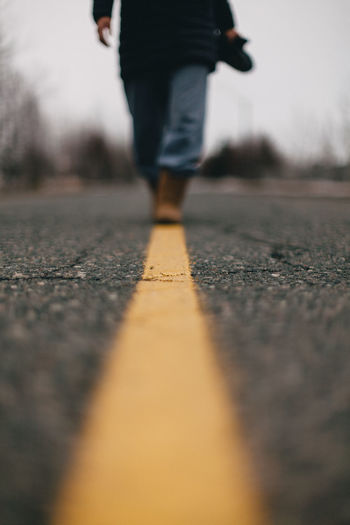 Low angle view of woman walking along yellow line on road.