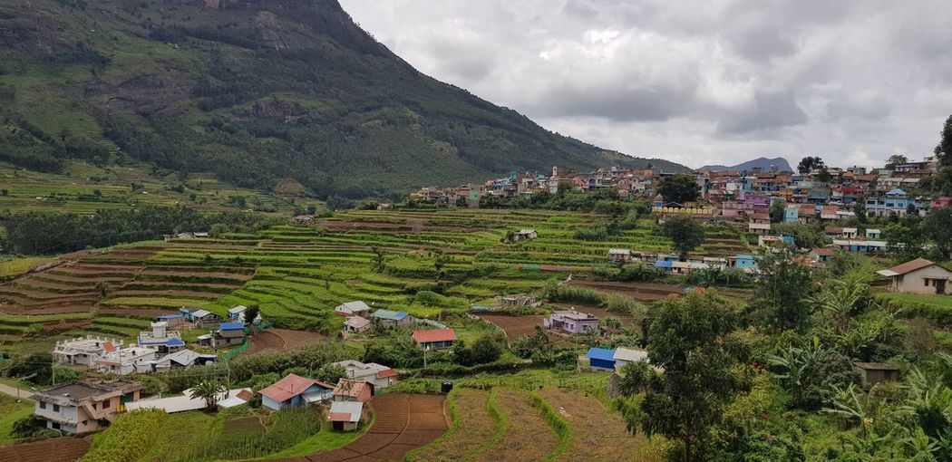 Scenic View Of Village And Houses Against Sky