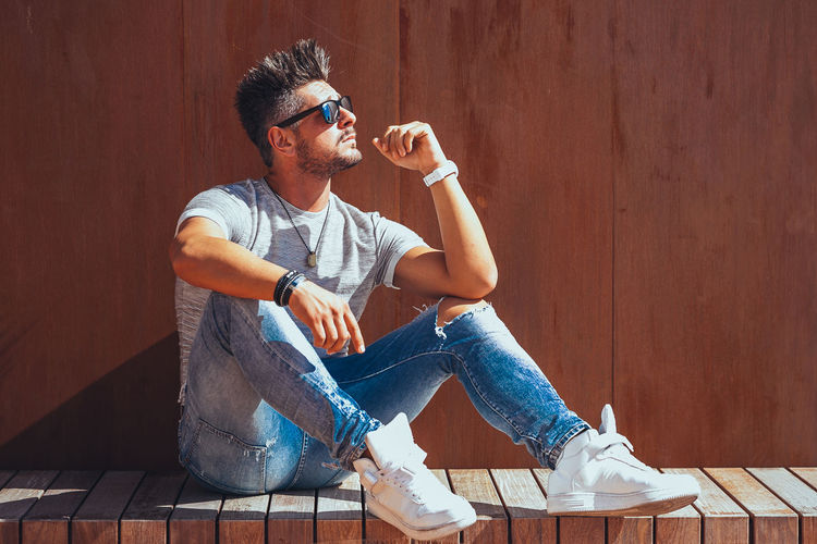 Casual Clothing Sitting Young Men One Person Glasses Real People Young Adult Full Length Leisure Activity Lifestyles Wood - Material Men Front View Fashion Looking Eyeglasses  Day Wall - Building Feature Jeans