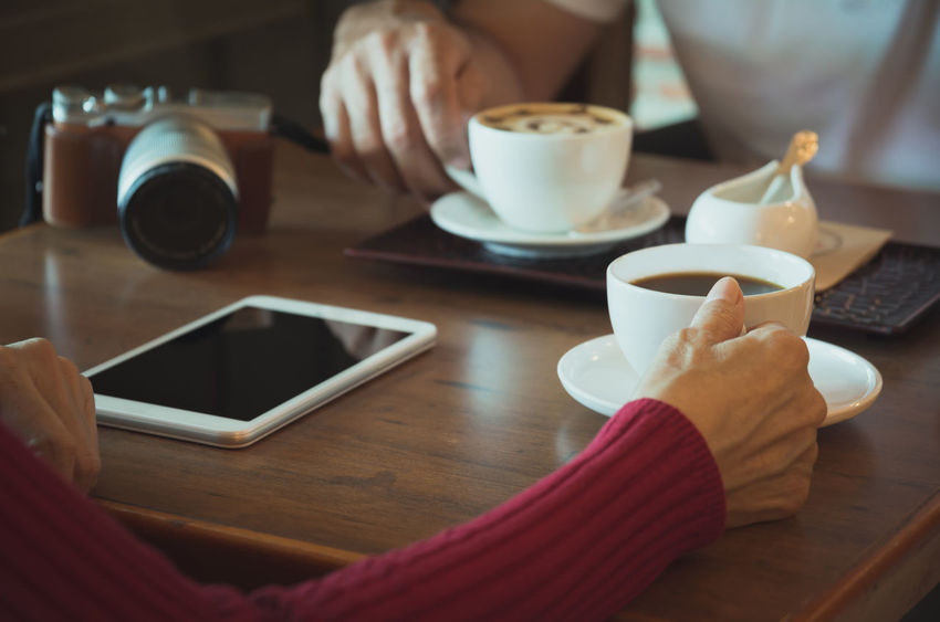 Female with tablet and camera coffee cup on wooden table. Table Drink Mug Cup Coffee Cup Human Hand Coffee Refreshment Food And Drink Hand Coffee - Drink Technology Wireless Technology Real People Connection Human Body Part One Person Indoors  Holding Lifestyles Saucer Crockery Hot Drink Tea Cup