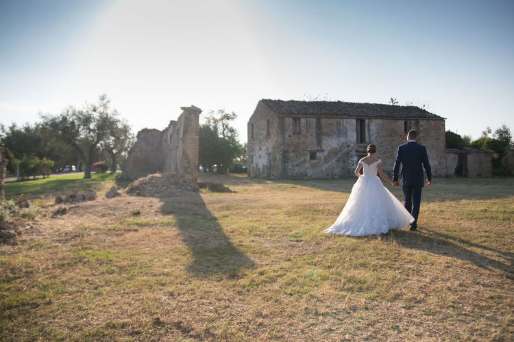 Full length rear view of newlywed couple walking by field by abandoned house against clear sky