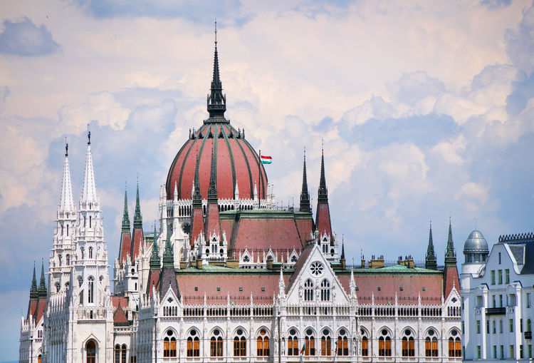 Low angle view of hungarian parliament building against cloudy sky in city