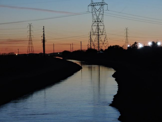 Sunset reflection Reflection Silhouette Sunset Electricity Pylon Water Sky Tree Electricity  Power Supply Power Line  Nature Scenics Outdoors No People Connection Beauty In Nature Technology