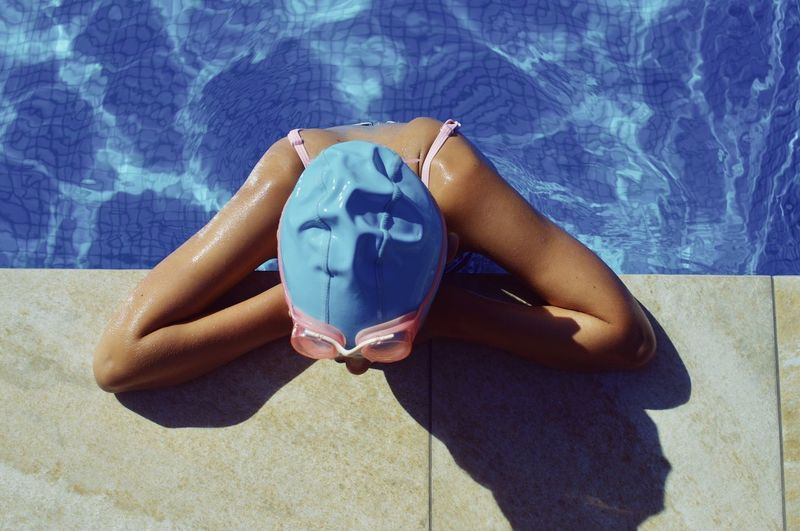 High angle view of girl sitting in swimming pool