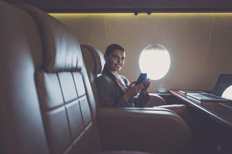 Smiling businesswoman using laptop in airplane