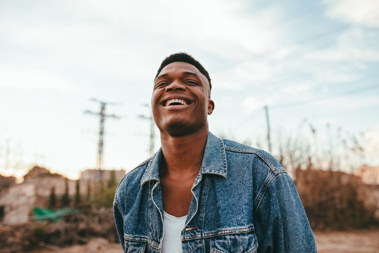 Portrait of smiling young man standing against sky