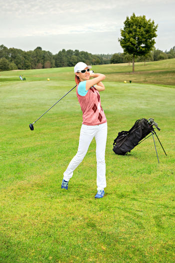 Full length of mature woman playing golf on grassy field against cloudy sky