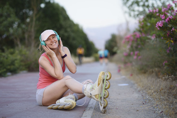 Blond girl wearing a pale pink cap and sports clothes sitting on the woman getting ready for skating in the park with her headphones on listening to the music. Adult Beautiful Woman Casual Clothing Day Focus On Foreground Full Length Hairstyle Hat Leisure Activity Lifestyles Looking At Camera One Person Outdoors Plant Portrait Real People Sitting Smiling Women Young Adult Young Women
